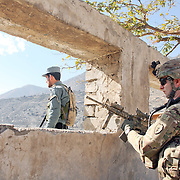 A member of the Afghan National Police stands guard with a member of the 2-27 Wolfhounds in front of the women's school where a water filtration demonstration given by Waves For Water and the US Military in the village of Nari, Kunar Province of Eastern Afghanistan.