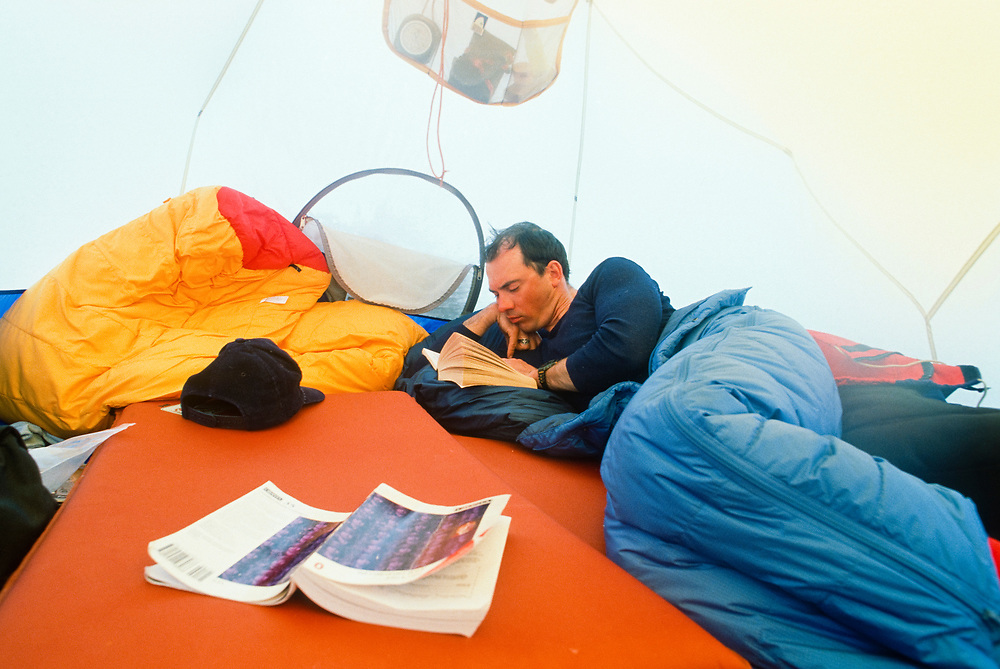 Alaska. Climber Rick Ford reads during stormy day while tent-bound a 11,000' on Denali. MR