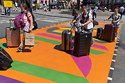 A travelling family push their wheelie suitcases over the multi-coloured markings of a crossing at Piccadilly Circus, on 16th July 2021, in London, England.