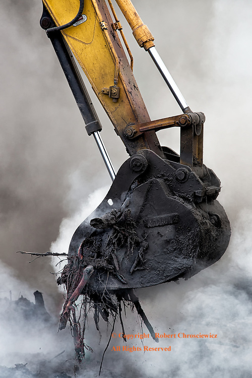 Held: An excavators' bucket transports its load through the waves of smoke that obscures the work site, Aldergrove British Columbia, Canada.