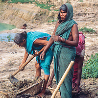 Older women dig mud as they help dig a fish pond to help feed their neighbors at Mirpur Destitute Camp near Dhaka, Bangladesh, a population left homeless after a cyclone and 1971 war of indepence.