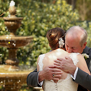 A father sees his daughter for the first time in her wedding dress and hugs her before walking her down the aisle for the ceremony in Columbia, S.C.    ©Travis Bell Photography
