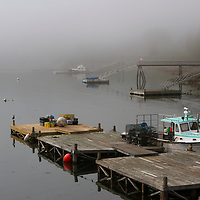 Coastal Maine working harbor photography on a foggy morning in Northeast Harbor, ME. Northeast Harbor is a scenic New England working harbor village filled with lobster boats, dories, and pleasure boat. It is especially photogenic on a fog filled morning. I arrived early to photograph the boats anchored in the Atlantic Ocean before the sun was burning off the fog. <br />