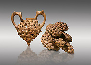 Hittite terra cotta two handled vessel and a ritual vessel in the shape of a bunch of grapes - 16th century BC - Hattusa ( Bogazkoy ) - Museum of Anatolian Civilisations, Ankara, Turkey . Against gray background .<br /> <br /> If you prefer to buy from our ALAMY STOCK LIBRARY page at https://www.alamy.com/portfolio/paul-williams-funkystock/hittite-art-antiquities.html  - Type Hattusa into the LOWER SEARCH WITHIN GALLERY box. Refine search by adding background colour, place, museum etc<br /> <br /> Visit our HITTITE PHOTO COLLECTIONS for more photos to download or buy as wall art prints https://funkystock.photoshelter.com/gallery-collection/The-Hittites-Art-Artefacts-Antiquities-Historic-Sites-Pictures-Images-of/C0000NUBSMhSc3Oo