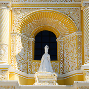 Alcove with stastue in the distinctive  and ornate yellow and white exterior of the Iglesia y Convento de Nuestra Senora de la Merced in downtown Antigua, Guatemala.