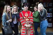 Man dressed as a Beefeater pulls a silly face outside a tourist shop in central London, UK. A group of girls, in town for the day, laugh as they have their picture taking with the man who fools about.