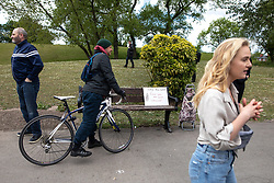 """© Licensed to London News Pictures. 16/05/2020. Manchester, UK. Placards reading """" No mandatory vaccines """" , """" Beware Poison """" """" No 5G """" and """" Hey Bill Gates Fuck you and your vaccine """" on a bench at the demonstration . An anti-lockdown, """"mass gathering"""" demonstration is held in Platt Fields Park in protest at government measures to control the spread of Covid-19. A group calling itself the UK Freedom Movement has organised a series of demonstrations across the UK. Photo credit: Joel Goodman/LNP"""