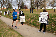 """20 NOVEMBER 2020 - DES MOINES, IOWA: A jogger runs past a protest in front of the Iowa Governor's Mansion. About 20 people participated in a protest in front of the Iowa Governor's Mansion Friday. They called on Governor Kim Reynolds to immediately issue a comprehensive mask mandate across Iowa. Reynolds, a Republican, has ordered a partial mask mandate that excuses some congregate settings, like classrooms. Iowa has one of the highest per capita COVID-19 infection rates in the country and is dealing with wide """"community spread"""" of the Coronavirus (SARS-CoV-2) throughout the state.        PHOTO BY JACK KURTZ"""