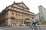 Teatro Colon opera theatre across the Avenida 9 Julio Avenue of ninth of July., a bicycle with a young man in the foreground. Buenos Aires Argentina, South America