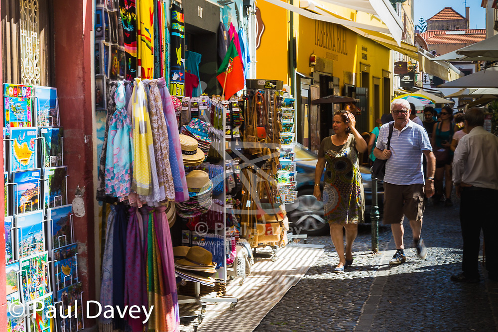 Tourists are tempted by colourful displays in the Old Town area of Funchal, Madeira. MADEIRA, September 26 2018. © Paul Davey