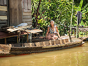 30 SEPTEMBER 2016 - SAI NOI, AYUTTHAYA, THAILAND:  A woman sits on the porch of her flooded home in Sai Noi. The Chao Phraya River, the largest river that runs through central Thailand, has hit flood stage in several areas in Ayutthaya and Ang Thong provinces. Villages along the river are flooded and farms are losing their crops due to the flood. This is the same area that was devastated by floods in 2011, but the floods this year are not expected to be as severe. The floods are being fed by water released from upstream dams. The water is being released to make room for heavy rains expected in October.     PHOTO BY JACK KURTZ