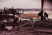 Safety Boss of Canada workers capping an oil well after they extinguished the fire. The burning Al Burgan oil fields in Kuwait after the end of the Gulf War in May of 1991 were covered in oil that rained down from the clouds of oil smoke and oil shooting into the air after a fire had been extinguished. More than 700 wells were set ablaze by retreating Iraqi troops creating the largest man-made environmental disaster in history. Photo taken on July 11, 1991.