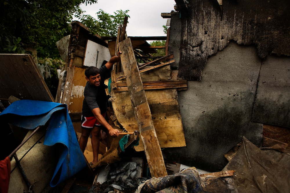 A man works to tear apart a home that he built by hand, the day before the relocation in Nova Gazela.