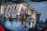 Days before the Chancellor Rishi Sunak delivers his Budget, thedistorted architecture Bank of England is seen reflected in the windscreen of a London bus which is driving through the City of London, the capital's financial district, on 1st March 2021, in London, England.