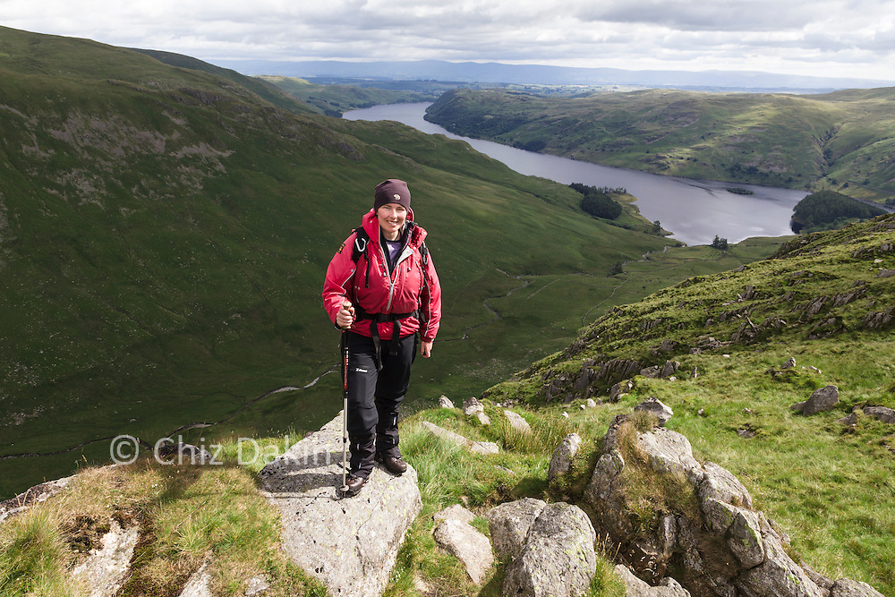 Walker on rocks on the ridge of Rough Crag, looking down Riggindale and Haweswater Reservoir