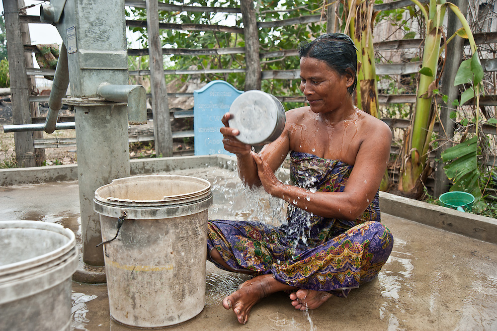 """Another handpump was provided to a community so far from a source of water that the women could only farm half each day, because they needed to fetch water in the afternoon. Woman alone bathing at pump is Nget Lam (53).  Thirty families use this well.  Quote from Nget Lam:  """"Before I could only haul 5 kilos of water for my family of three.  It's not enough.  Sometimes we would have to go days without bathing. Now water is my joy""""."""