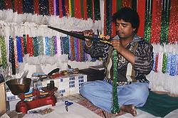 Asia, Nepal, Kathmandu, Durbar Square, man stringing colorful beads in stall at Indra Chowk market
