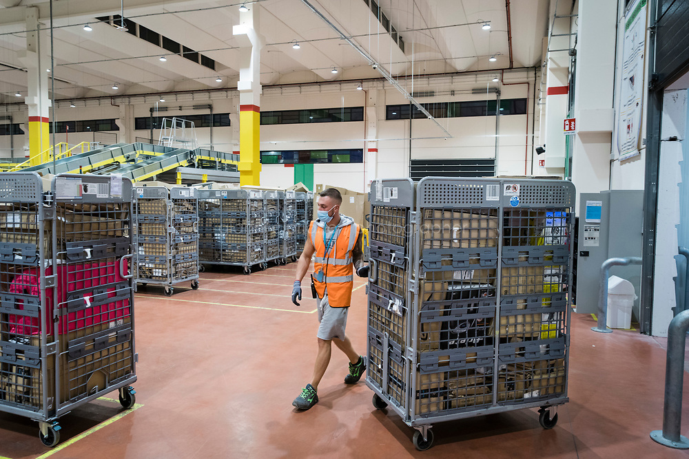 ARZANO, ITALY - 18 SEPTEMBER 2020: A Water Spider unloads a truck of Amazon packages that will be processed at the Amazon delivery station in Arzano, just outside Naples, Italy, on September 18th 2020.<br /> <br /> Opened in 2019, the Amazon delivery station in Arzano was the first to open in Southern Italy. Here, an average of 30,000 to 50,000 Amazon packages are processed and delivered in the region.<br /> <br />    plans to open two new fulfillment centers and seven delivery stations. Roughly 1,600 more people will be hired by the end of the year, pushing its full-time work force in Italy to 8,500 from less than 200 in 2011. <br /> <br /> Amazon has been one of the biggest winners in the pandemic as people in its most established markets — the United States, Germany and Britain — have turned to it to buy everything from toilet paper to board games. What has been less noticed is that people in countries that had traditionally resisted the e-commerce giant are now also falling into Amazon's grasp .<br /> The shift has been particularly pronounced in Italy, which was one of the first countries hard hit by the virus. Italians have traditionally preferred to shop at local stores and pay cash. But after the government imposed Europe's first nationwide virus lockdown, Italians began shopping online in record numbers. <br /> 75 percent of Italians shopped online during the lockdown. In 2020, total online sales are estimated to grow 26 percent to a record 22.7 billion euros, according to researchers from Polytechnic University of Milan.