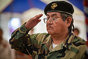 "13 JULY 2012 - FT DEFIANCE, AZ:  A Navajo veteran of the US Marine Corps salutes during the veterans' service at the 23rd annual Navajo Nation Camp Meeting in Ft. Defiance, north of Window Rock, AZ, on the Navajo reservation. Preachers from across the Navajo Nation, and the western US, come to Navajo Nation Camp Meeting to preach an evangelical form of Christianity. Evangelical Christians make up a growing part of the reservation - there are now more than a hundred camp meetings and tent revivals on the reservation every year. The camp meeting in Ft. Defiance draws nearly 200 people each night of its six day run. Many of the attendees convert to evangelical Christianity from traditional Navajo beliefs, Catholicism or Mormonism. ""Camp meetings"" are a form of Protestant Christian religious services originating in Britain and once common in rural parts of the United States. People would travel a great distance to a particular site to camp out, listen to itinerant preachers, and pray. This suited the rural life, before cars and highways were common, because rural areas often lacked traditional churches. PHOTO BY JACK KURTZ"