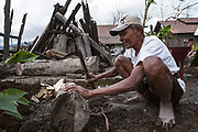 A man chops wood in the village hit by the Mt Merapi 2010 eruption.