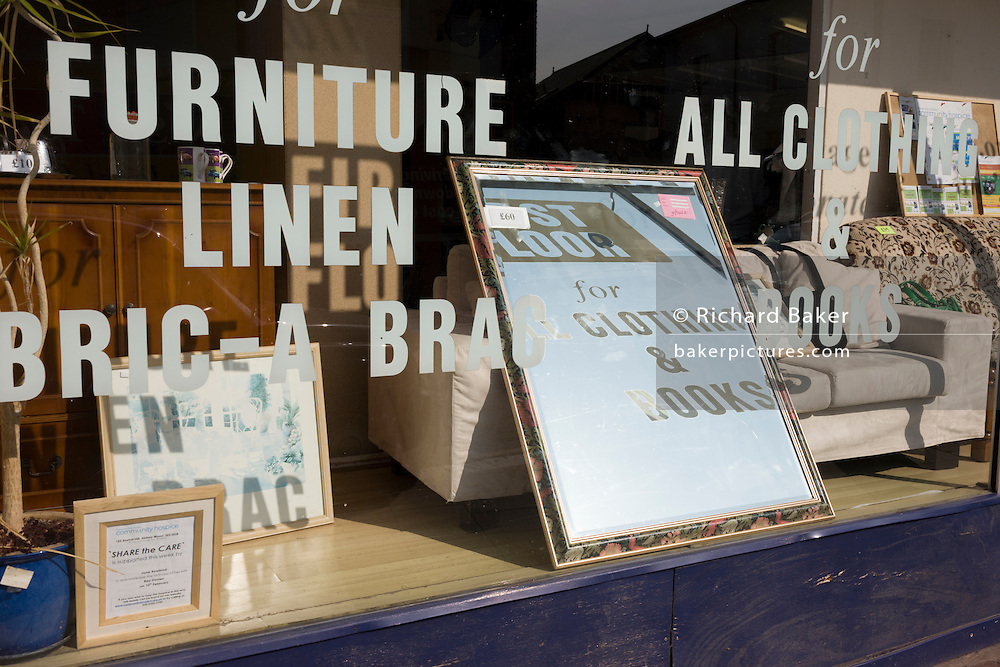 Reflections of lettering and writing on a charity shop window selling briac-a-brac on a London high-street.