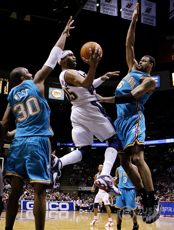 The Nets' Vince Carter (C) drives to the basket past the Hornets' David West (L) and Tyson Chandler (R) during the second half of the New Orleans/Oklahoma City Hornets' 111-107 victory over the New Jersey Nets at Continental Airlines Arena in East Rutherford, New Jersey on Wednesday 21 February 2007.