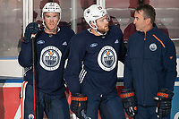 KELOWNA, BC - SEPTEMBER 22:  Connor McDavid #97 and Leon Draisaitl #29 of the Edmonton Oilers stand at the boards with Associate Coach Jim Playfair during practice at Prospera Place on September 22, 2019 in Kelowna, Canada. (Photo by Marissa Baecker/Shoot the Breeze)