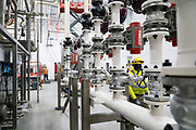 Employees walk past the CIP (clean-in-place) equipment at the Puris pea protein processing facility in Dawson, Minnesota, on Tuesday, June 8, 2021.