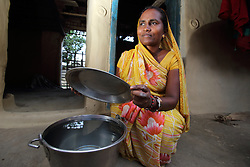 Jangali Ram  draws water from a tubewell and carries her water back to her home and covers it with a lid to keep it clean from dust, in Ganespur Community of Bastipur NEWAH WASH project Siraha, Udayapur District, Nepal.