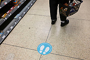 Supermarket social distancing sticker on the floor on 11th April 2020 in Birmingham, England, United Kingdom. Coronavirus or Covid-19 is a new respiratory illness that has not previously been seen in humans. While much or Europe has been placed into lockdown, the UK government has announced more stringent rules as part of their long term strategy, and in particular social distancing.