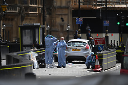 Forensic officers by the car that crashed into security barriers outside the Houses of Parliament, Westminster, London.