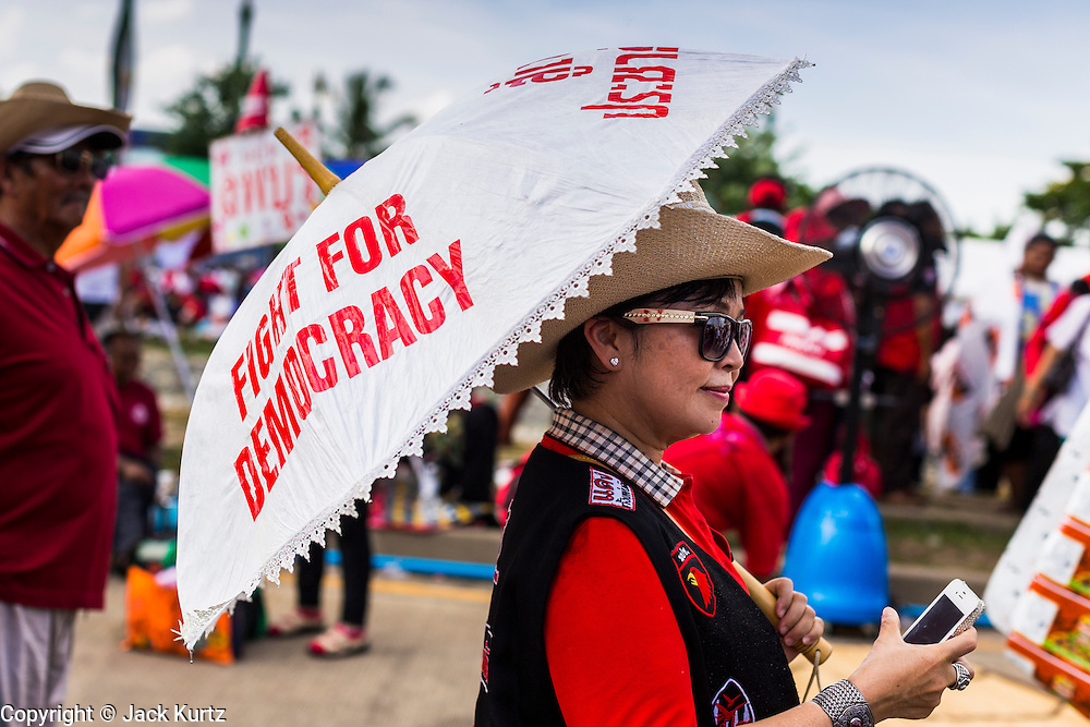 10 MAY 2014 - BANGKOK, THAILAND:  A Red Shirt with an umbrella makes a call on her cell phone. Thousands of Thai Red Shirts, members of the United Front for Democracy Against Dictatorship (UDD), members of the ruling Pheu Thai party and supporters of the government of ousted Prime Minister Yingluck Shinawatra are rallying on Aksa Road in the Bangkok suburbs. The government was ousted by a court ruling earlier in the week that deposed Yingluck because the judges said she acted unconstitutionally in a personnel matter early in her administration. Thailand now has no functioning government. Red Shirt leaders said at the rally Saturday that any attempt to impose an unelected government on Thailand could spark a civil war. This is the third consecutive popularly elected UDD supported government ousted by the courts in less than 10 years.   PHOTO BY JACK KURTZ