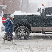 Woman walking in the street during a snowstorm because the sidewalks are covered with snow