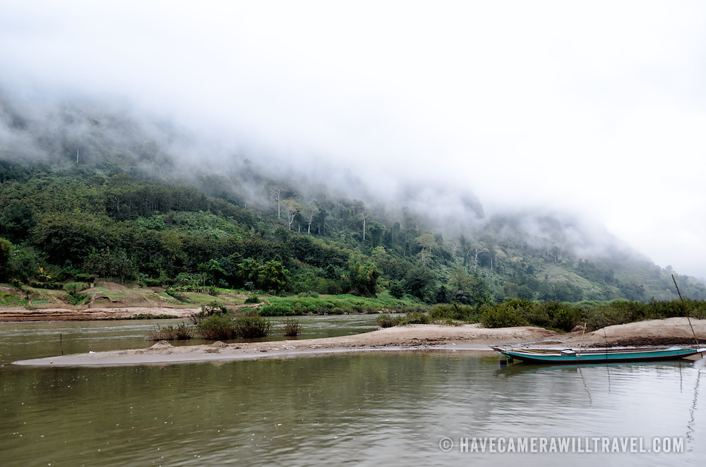 Mists roll shroud the steep limestone karsts along the banks of the Nam Ou (River Ou) in Nong Khiaw in norther Laos. Sanbanks in the middle of the river form small sand islands and protected moorings.