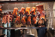 Chef hangs a piece of belly pork next to crispy Peking Ducks in the window of a Chinese restaurant in Chinatown, London. These ducks have been covered in spices and deep fried to giev them a glistening and crispy skin, a speciality of Chinese cooking.
