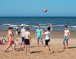 Portobello,Scotland, UK. 28 June, 2019. Warm temperatures and unbroken sunshine brought hundreds of people and families to enjoy this famous beach outside Edinburgh. Teenagers playing with football on the beach.