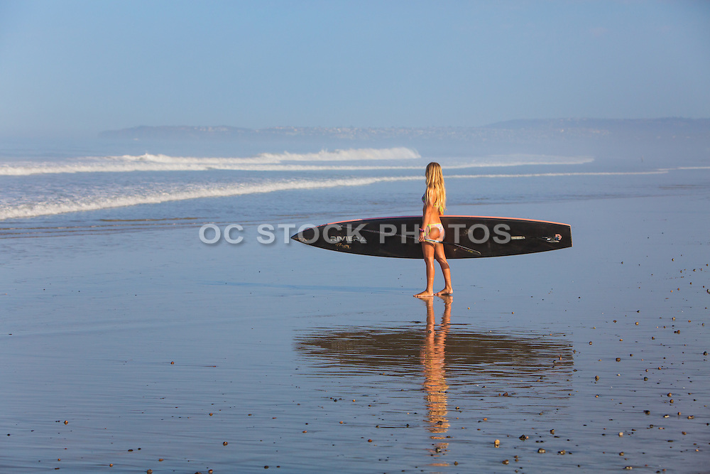 Teen Girl Standing on the Beach with Stand Up Paddle Board looking out at the Ocean in San Clemente
