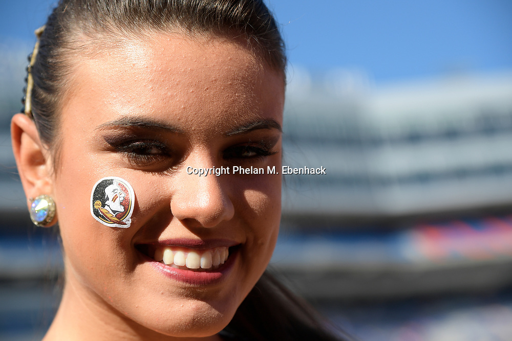A Florida State cheerleader displays a team logo on her face before an NCAA college football game against Florida Saturday, Nov. 25, 2017, in Gainesville, Fla. (Photo by Phelan M. Ebenhack)
