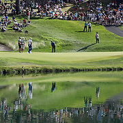 K.J. Choi, South Korea, plays a shot on the 16th green while reflected in a pond during the final round of the Travelers Championship at the TPC River Highlands, Cromwell, Connecticut, USA. 22nd June 2014. Photo Tim Clayton