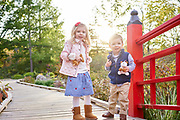 Family portrait session with the boy and girl standing on the bridge with red railing. Sun behind them looking at the camera.