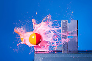 A paintball is fired directly at the vertical edge of a razor blade.