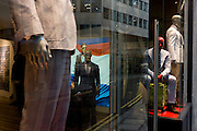 Mannequins displaying casual stylish menswear in window of City of London branch of Suit Supply.