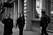 Pedestrians walk past a hair salon in Soho, New York, Tuesday, January 31, 2006.