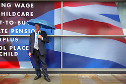 © Licensed to London News Pictures. 06/10/2015. Manchester, UK. A Conservative delegate taking a cigarette break outside Conservative Party Conference at Manchester Central convention centre on Tuesday, 6 October 2015. Photo credit: Tolga Akmen/LNP