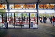 Nederland, Nijmegen, 25-10-2019 Op het station van deze stad staan mensen te wachten op de trein . De zon staat laag en geeft oranje licht .Foto: Flip Franssen