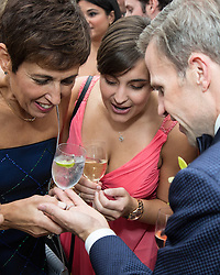 groom showing off his wedding ring to women at a party