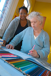 Art therapist working with a mental health patient at a drop in centre; Leeds Yorkshire UK
