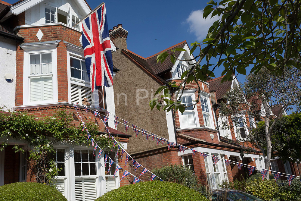 As the Coronavirus lockdown continues over the May Bank Holiday, the nation commemorates the 75th anniversary of VE Day Victory in Europe Day, the day that Germany officially surrendered in 1945 and in Dulwich, neighbours and residents emerge from their homes to party while still observing social distancing rules. A house has a large Union Jack and bunting hanging from a window, on 8th May 2020, in London, England.