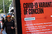 Covid-19 variant of concern public health NHS advertising board with just five more days to the official freedom day planned for the 19th July, people, many of whom are wearing face masks, come to the city centre retail shopping district on 14th July 2021 in Birmingham, United Kingdom. After months of lockdown, but with case numbers rising, in particular that of the Delta Variant, there is hope that life will start to return to normal, with restrictions like the compulsory wearing of face coverings in public spaces ending.