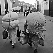 CEUTA, SPAIN - JUNE 27, 2010 : Two women carrying goods to pass to Morrocco at  the warehouses next to the cross border of El Biutz,  Ceuta. Spain. Thousands  of people are involved in transporting smuggled goods from Ceuta (an Spanish enclave on the North African coast) to Morocco, it is estimated that every day enter 10.000 porters, mostly women, that it make between three and five trips to Morocco with all types of products purchased on  the warehouse border area of El Biutz in Ceuta, Spain.( Photo by Jordi Cami )